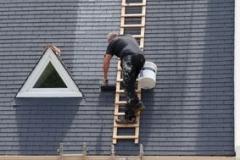 Ouvrier peignant le toit d'une maison